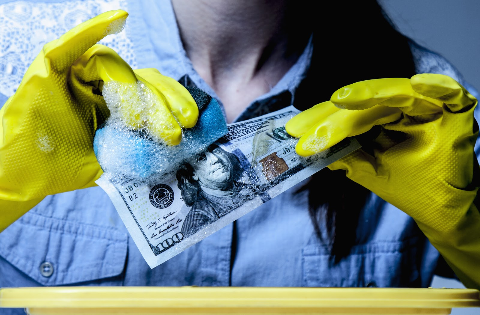 Credit vs. cash: A woman wearing rubber gloves washes a $100 bill