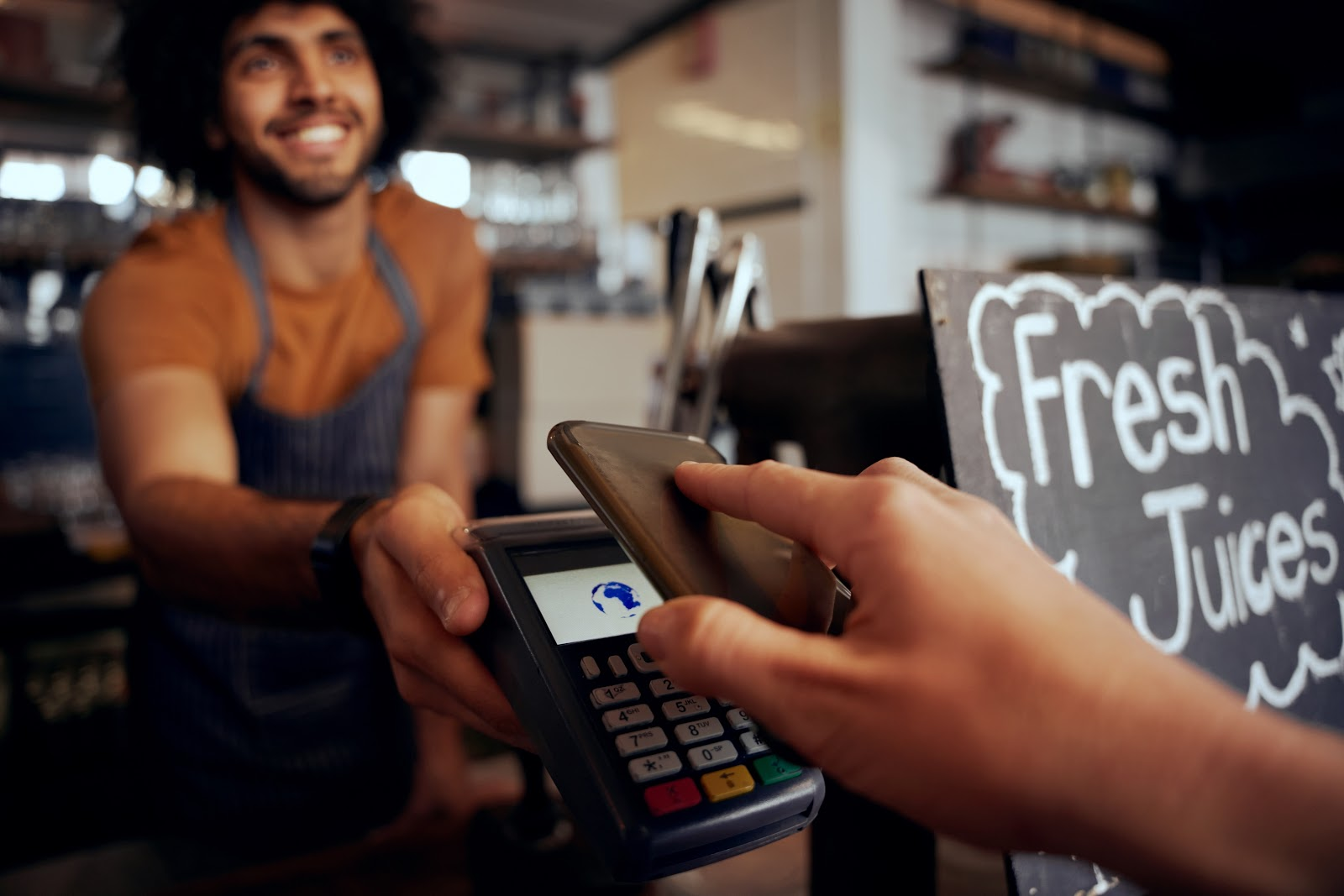 A person makes a contactless payment in a cafe
