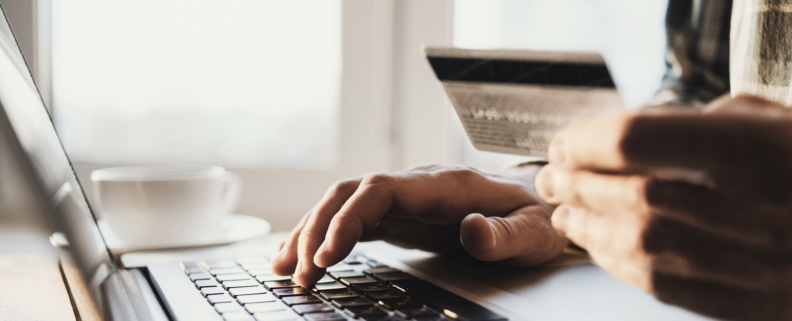 How much are credit card fees: A person holds a credit card and types on a laptop