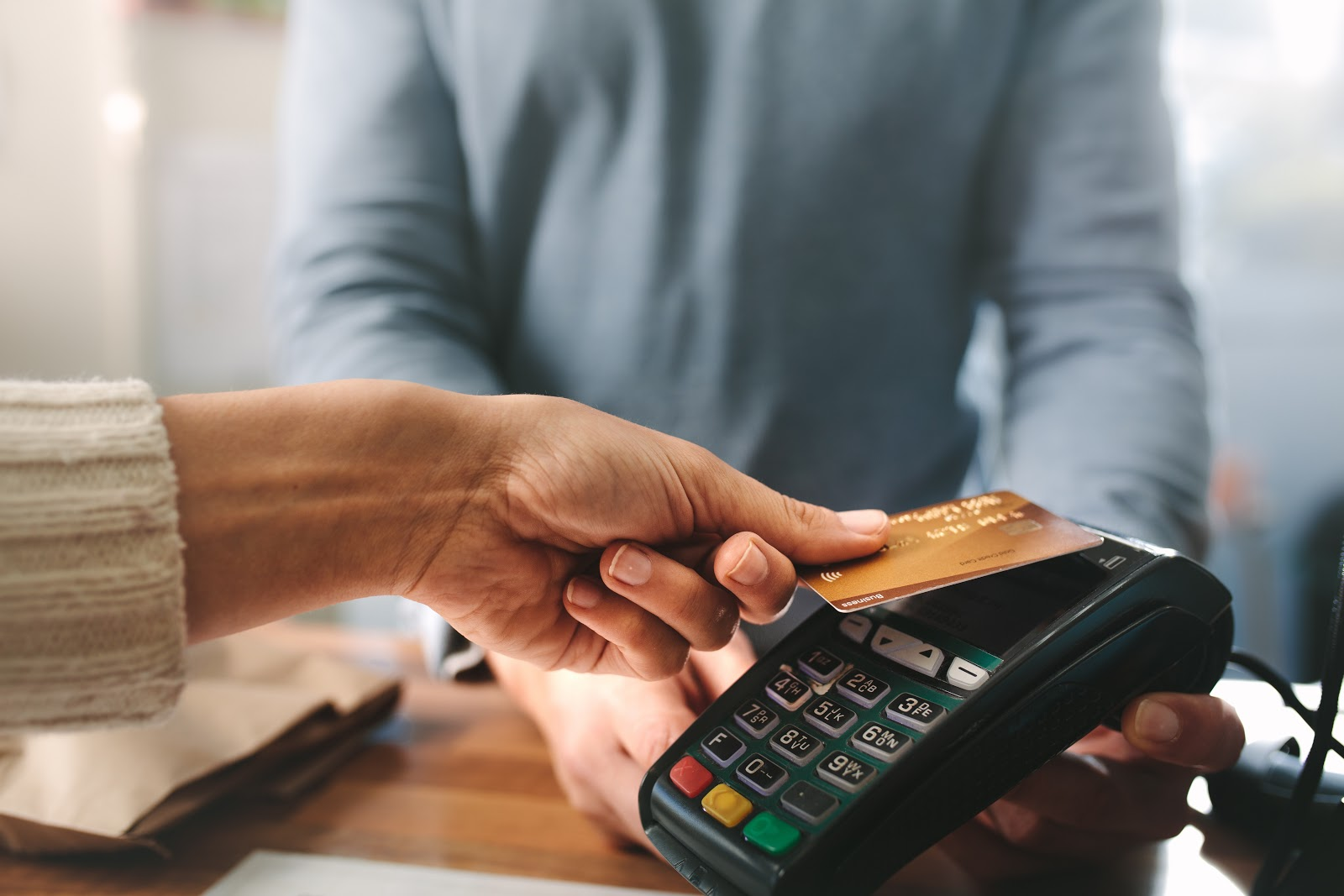 How much are credit card fees: A person using contactless credit card payment