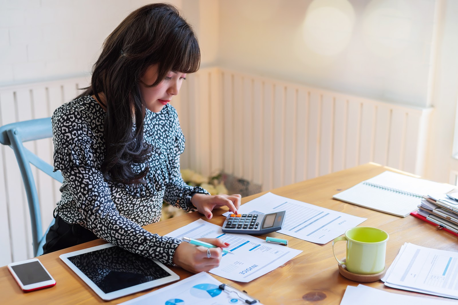 How to get a late fee waived: A woman uses a calculator while paying her bills
