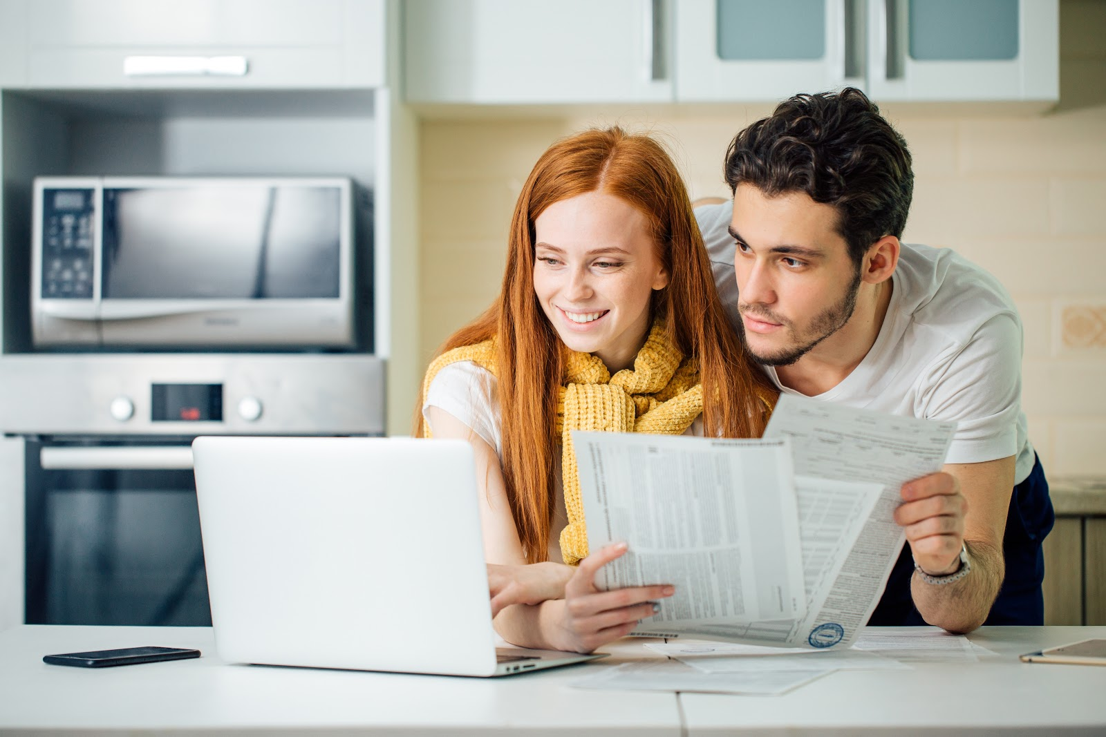 A couple uses a laptop to buy their bills