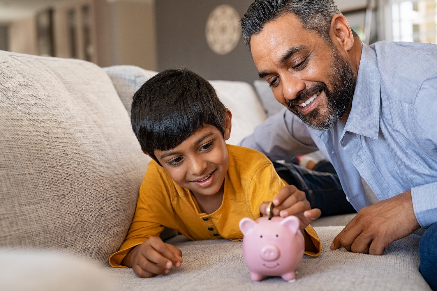 How to use your tax refund wisely: A man and his son put change in a piggy bank