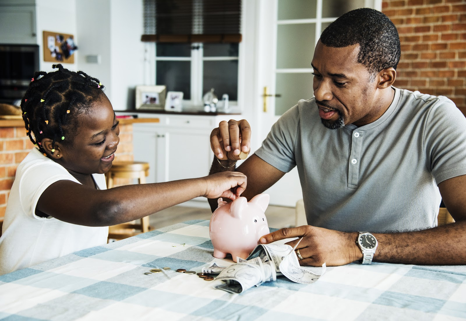 A father and daughter save money in a piggy bank