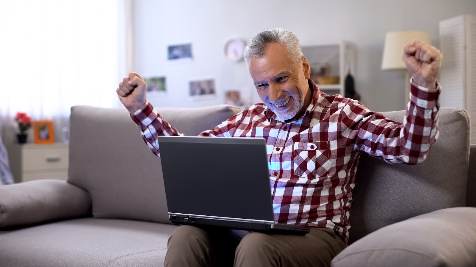 A man celebrates while looking at his laptop screen