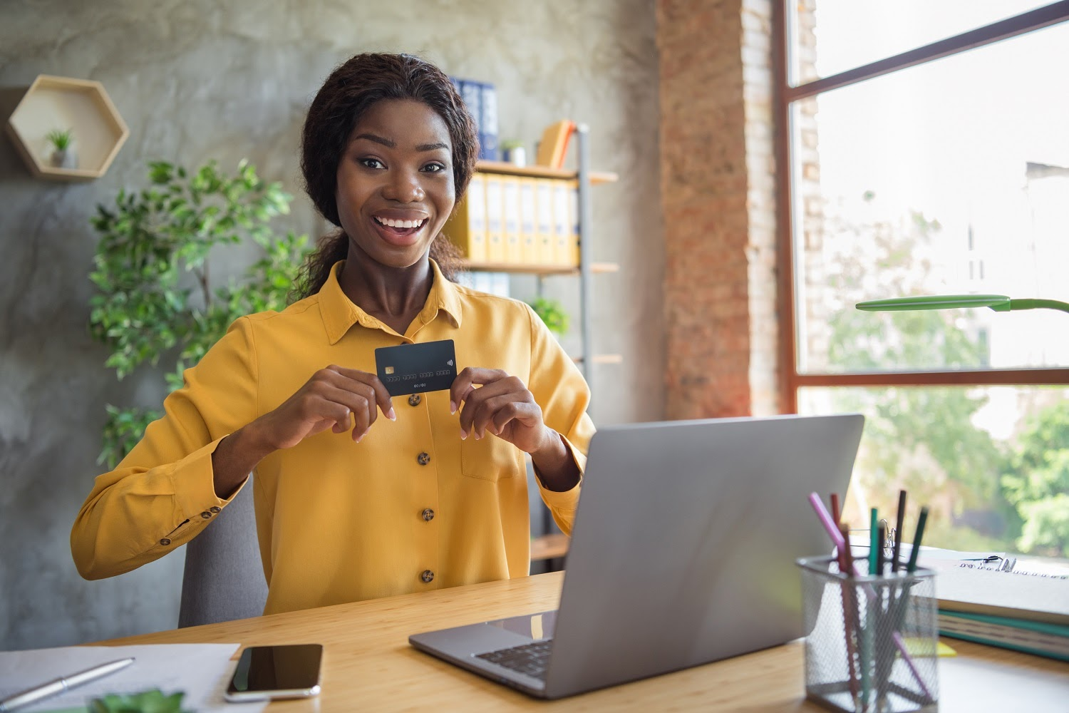 Smartest way to use a credit card: A smiling woman holds a credit card and sits at her desk