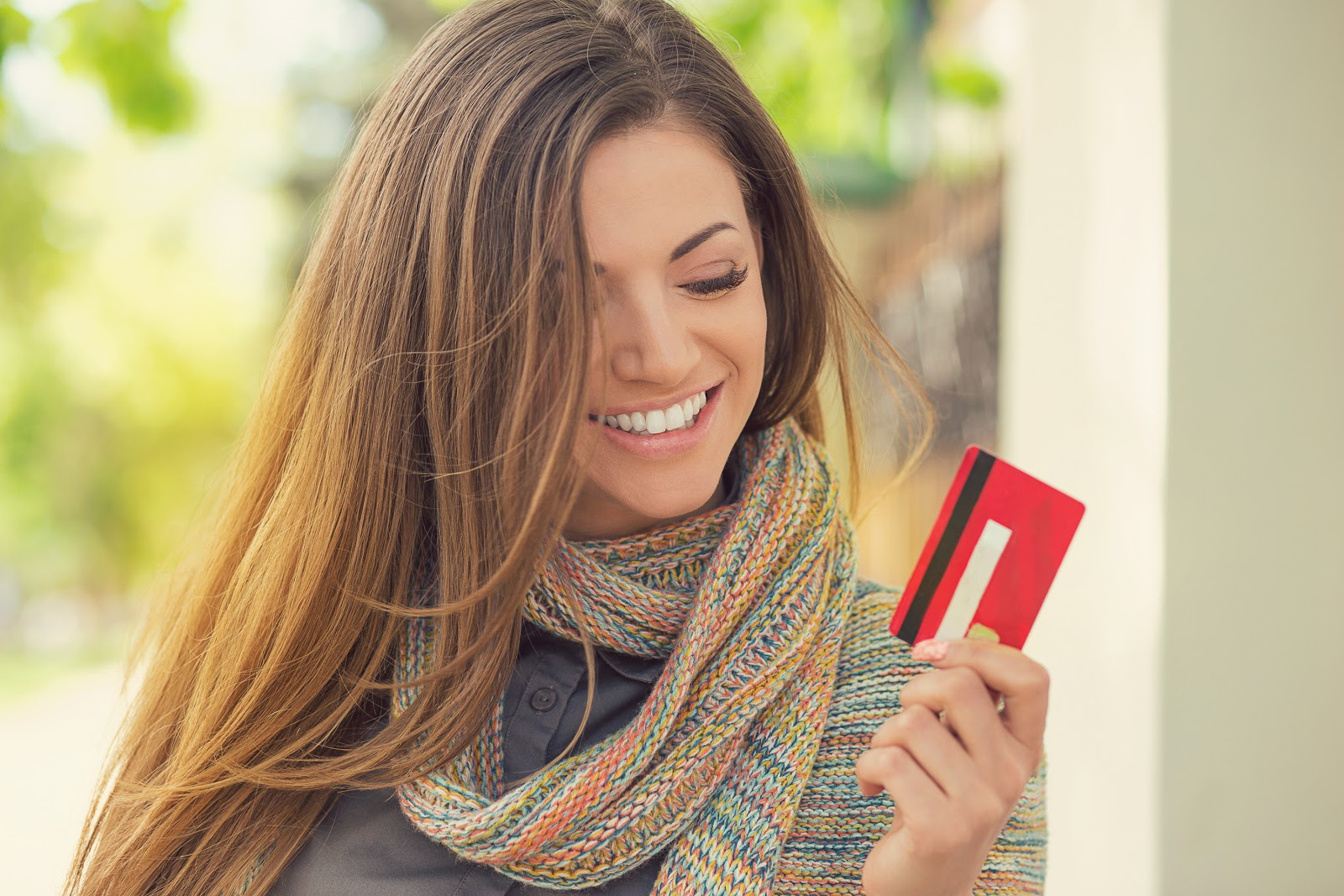 A smiling woman holds a credit card