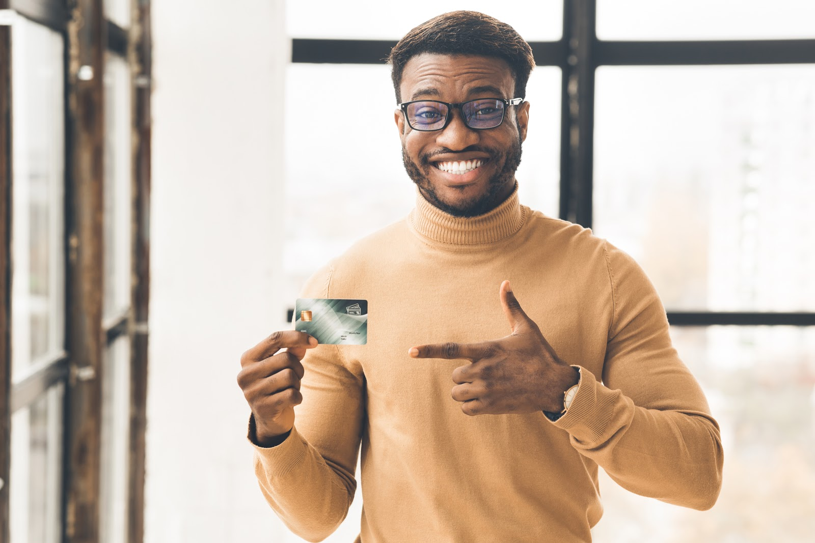 A man smiles and points at his credit card