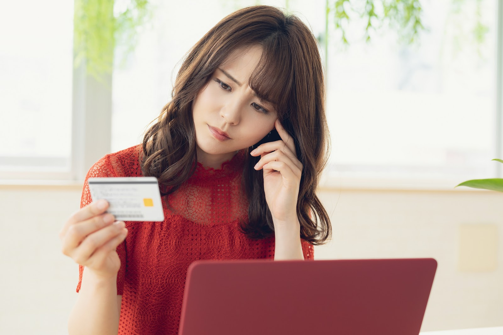 Can you pay a credit card with a credit card: A woman thinks and looks at her credit card