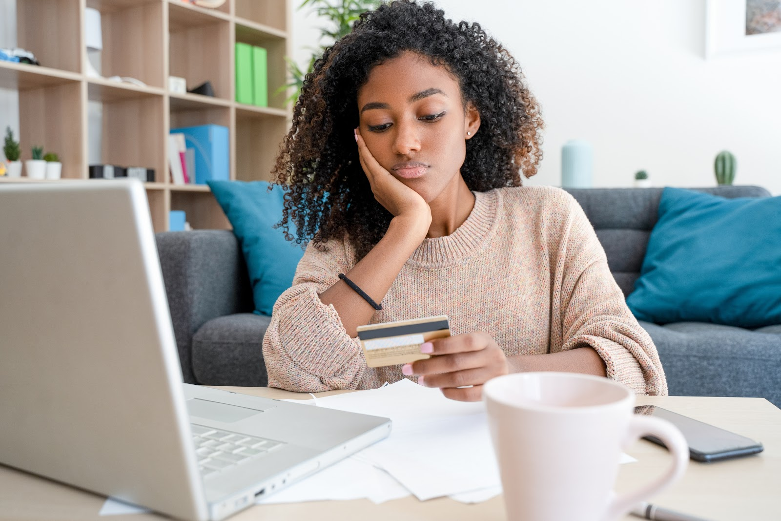 A woman sits in front of her laptop and holds her credit card