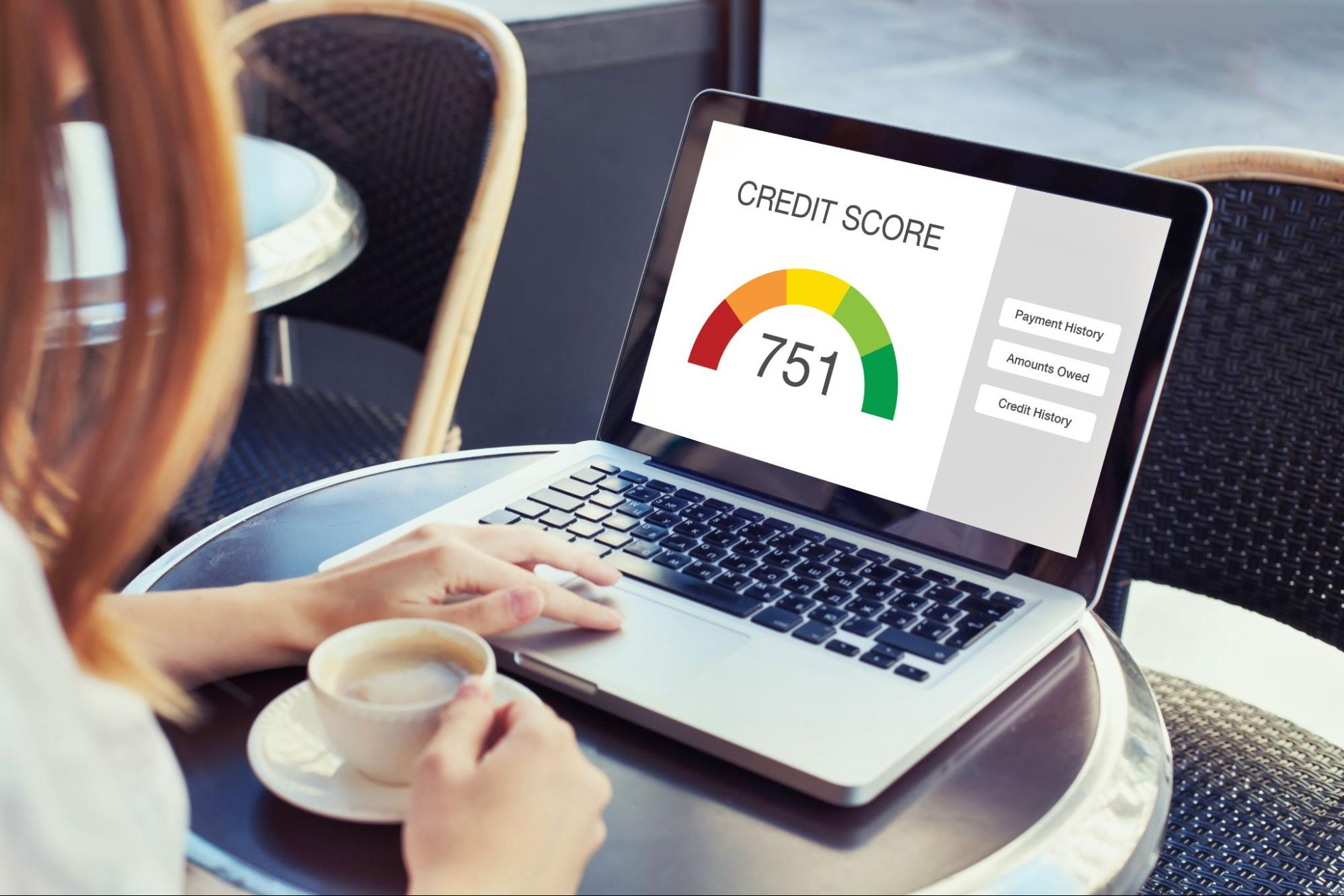 Credit utilization: A woman sits in a coffee shop and looks at her credit score on a laptop