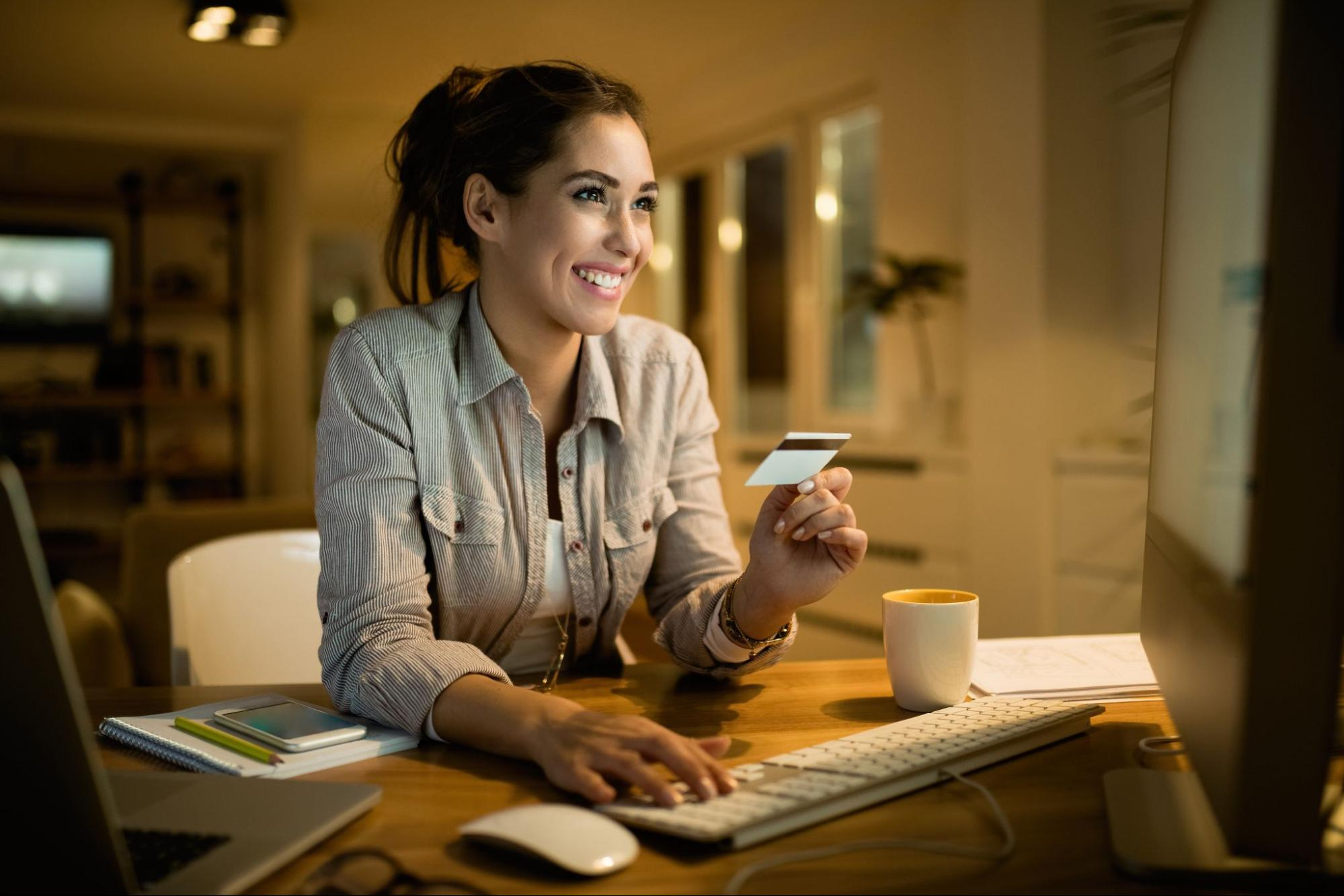 A smiling woman holds a credit card and types on a desktop computer