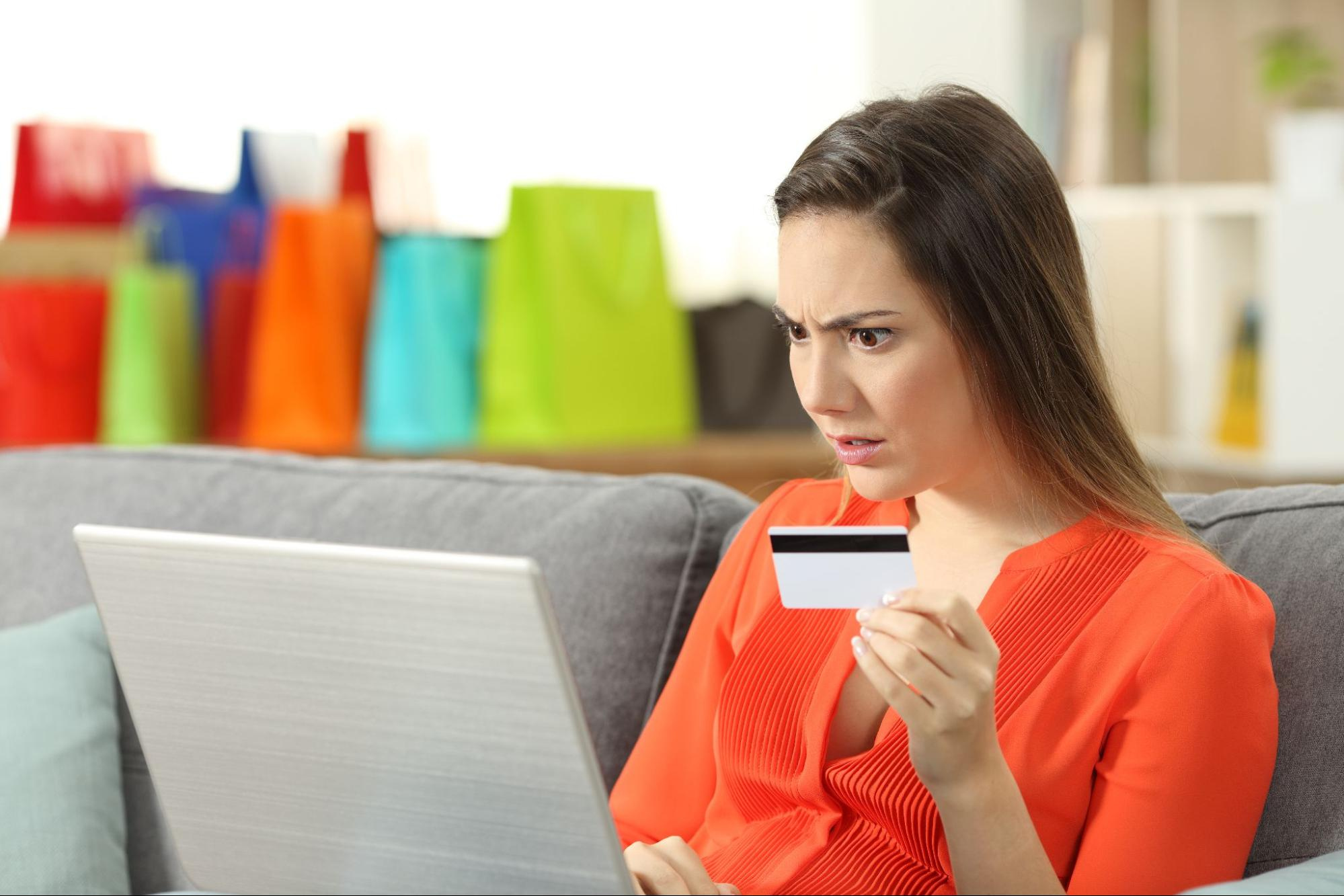 A shocked woman holds her credit card and looks at her laptop screen