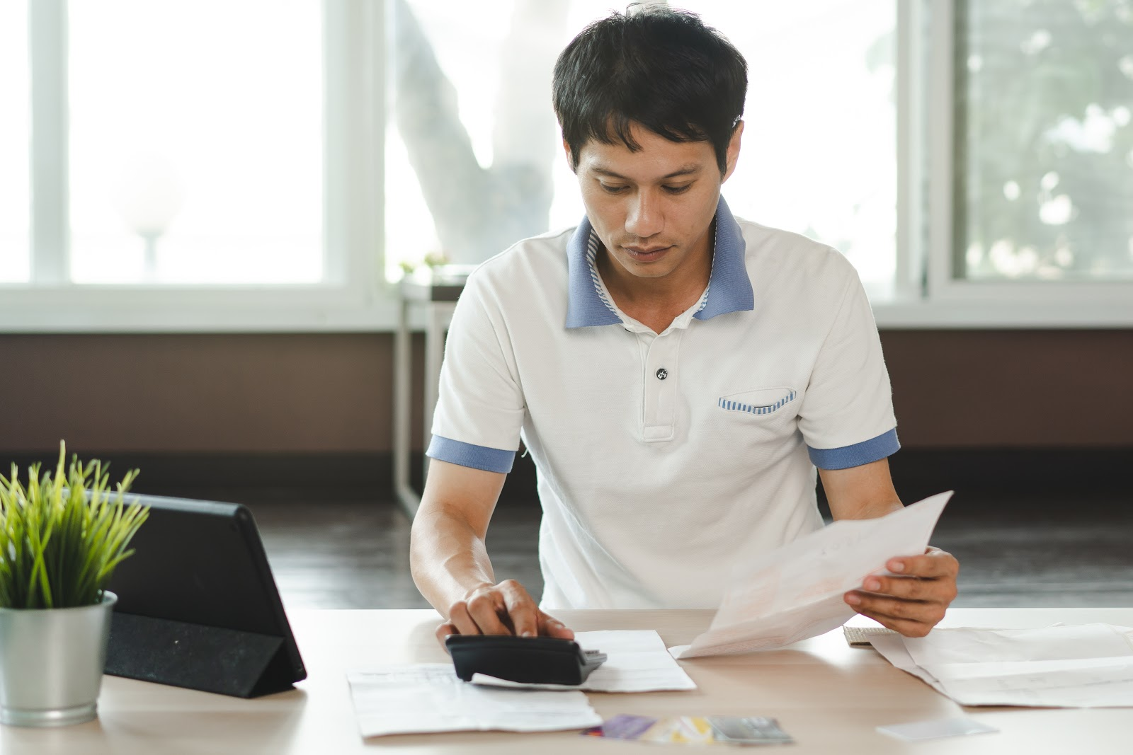 How to consolidate credit card debt on your own: A man calculates his bills