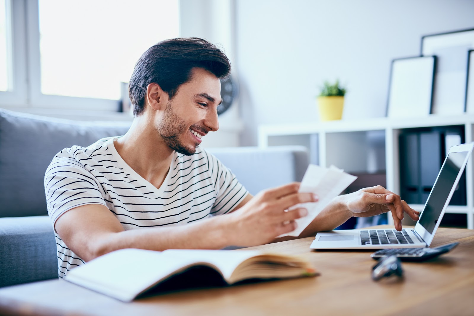 A smiling man pays his bills online