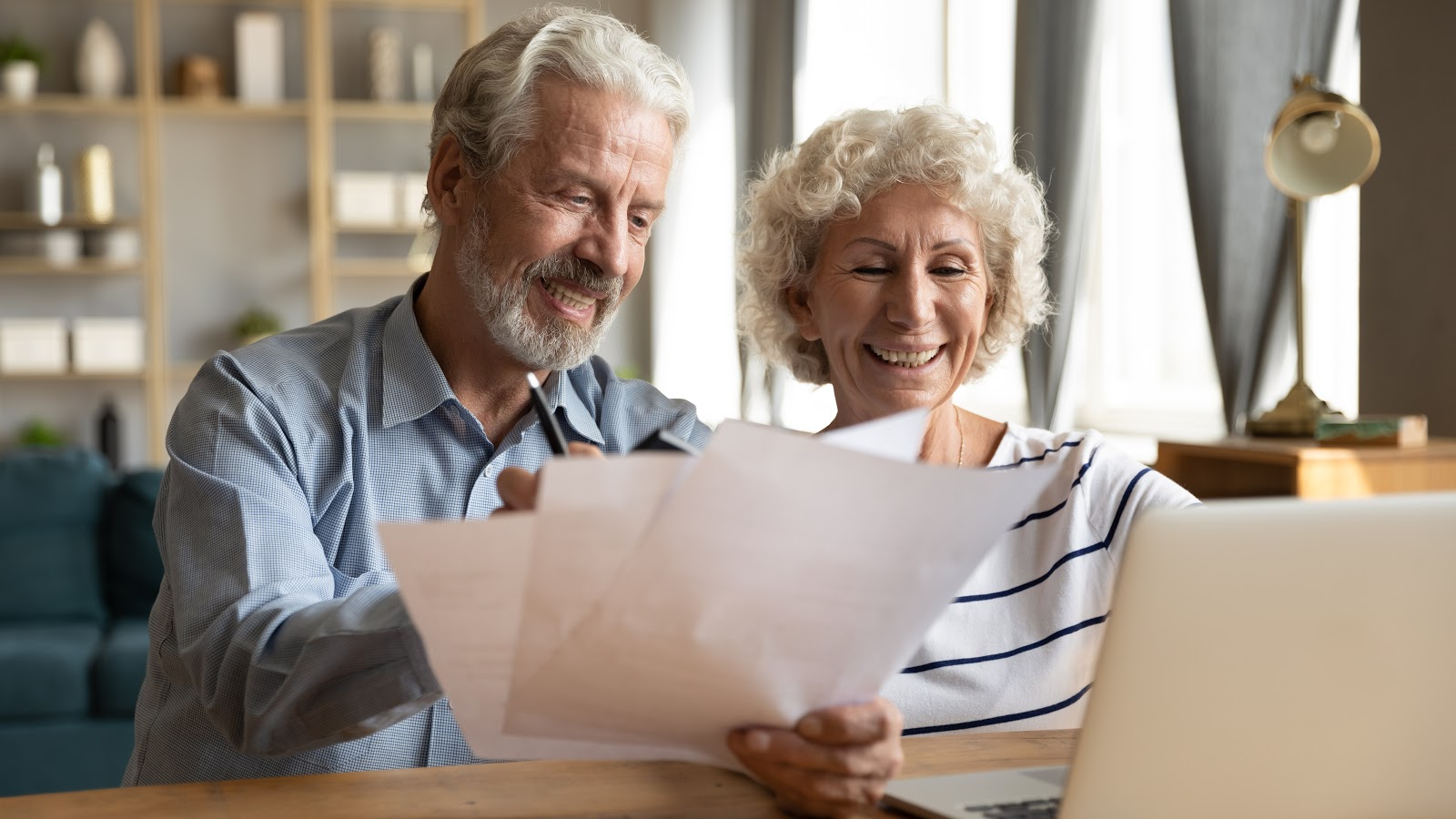 A smiling couple looks over their finances