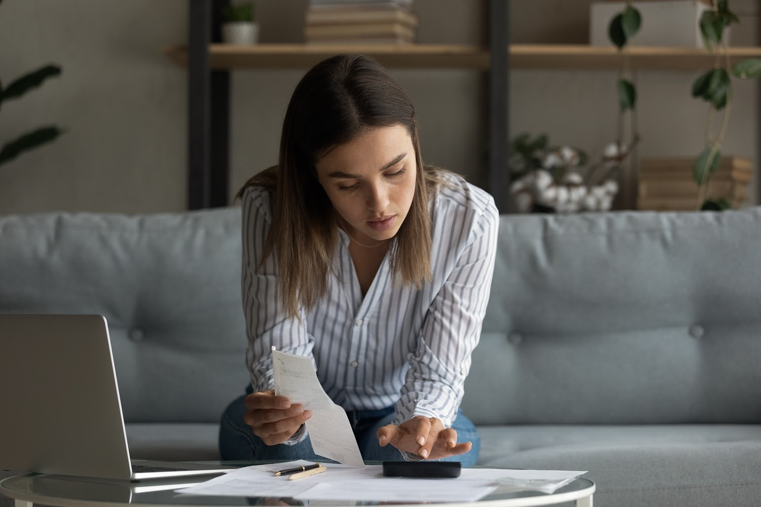 How to refinance credit card debt: A woman adds up receipts with a calculator
