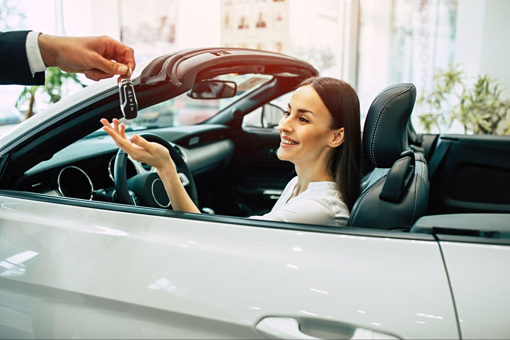 Depreciation: A woman sits in a brand-new car while the salesperson hands her the key