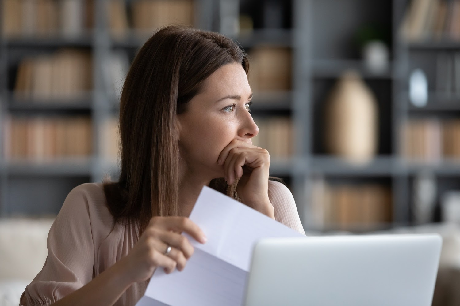 What is better bankruptcy or debt consolidation: A woman looks worried and holds a bill in her hand