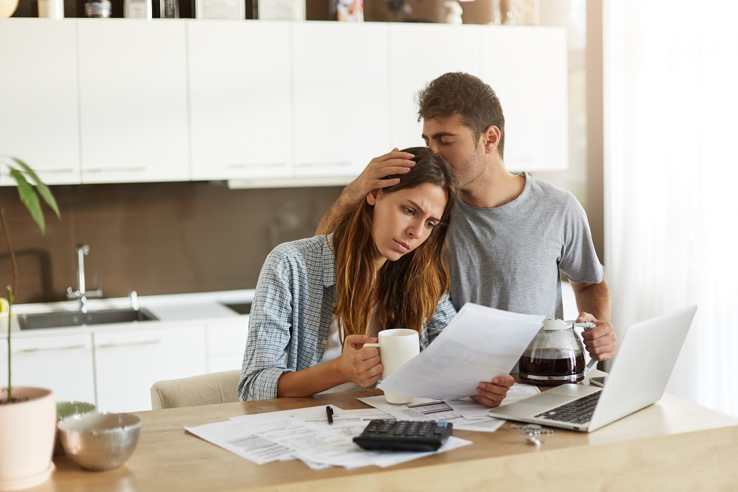 A husband comforts his worried wife while looking over their bills