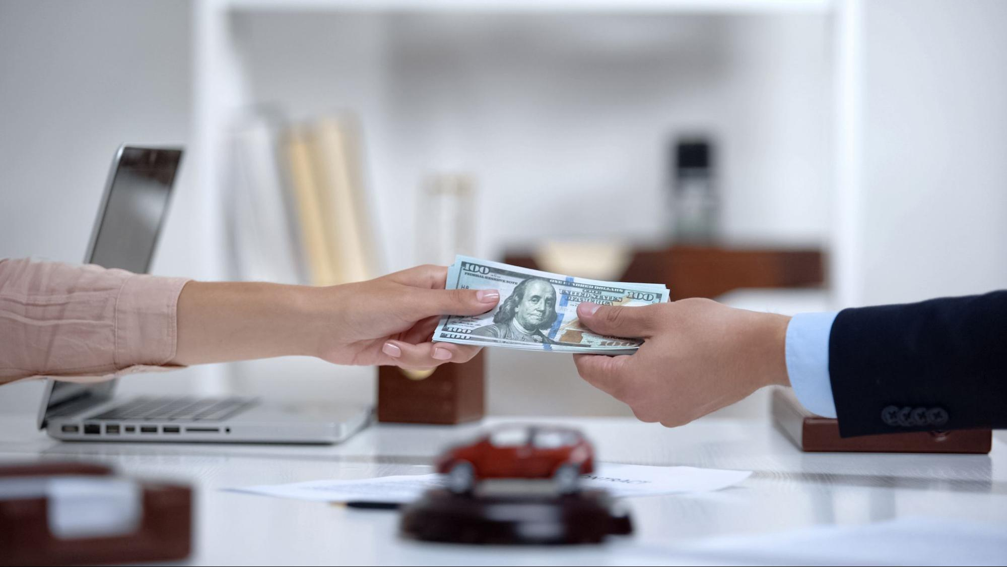 A woman hands over cash for a down payment
