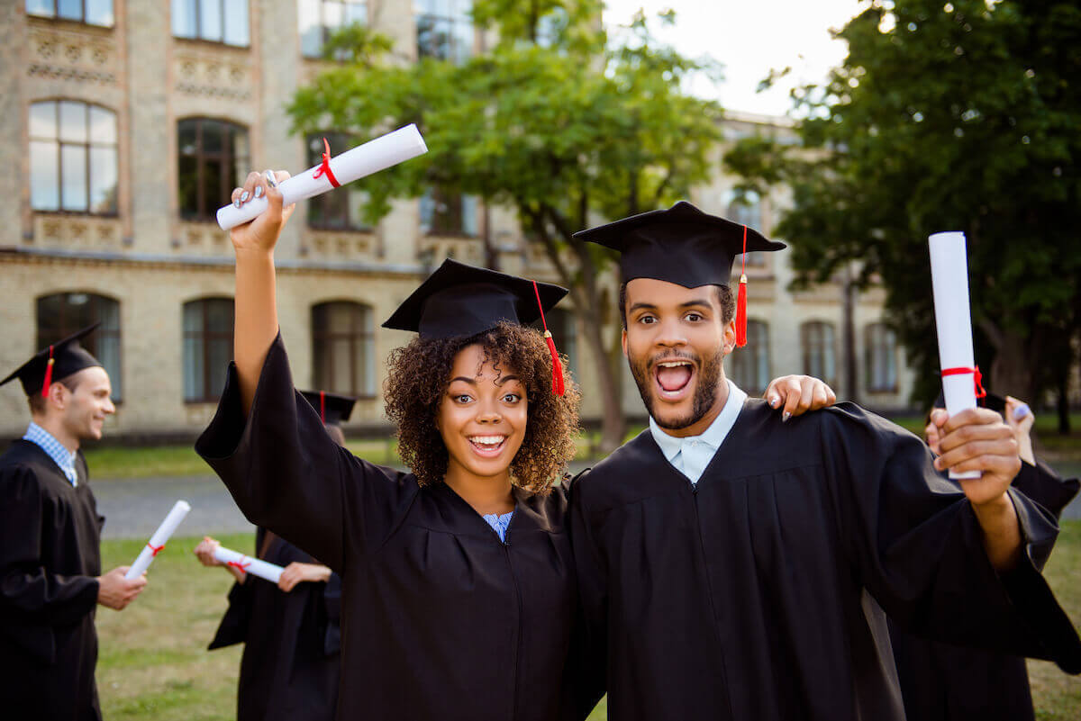 What is the average credit score of a college student: Two college grads wearing caps and gowns celebrate with their diplomas