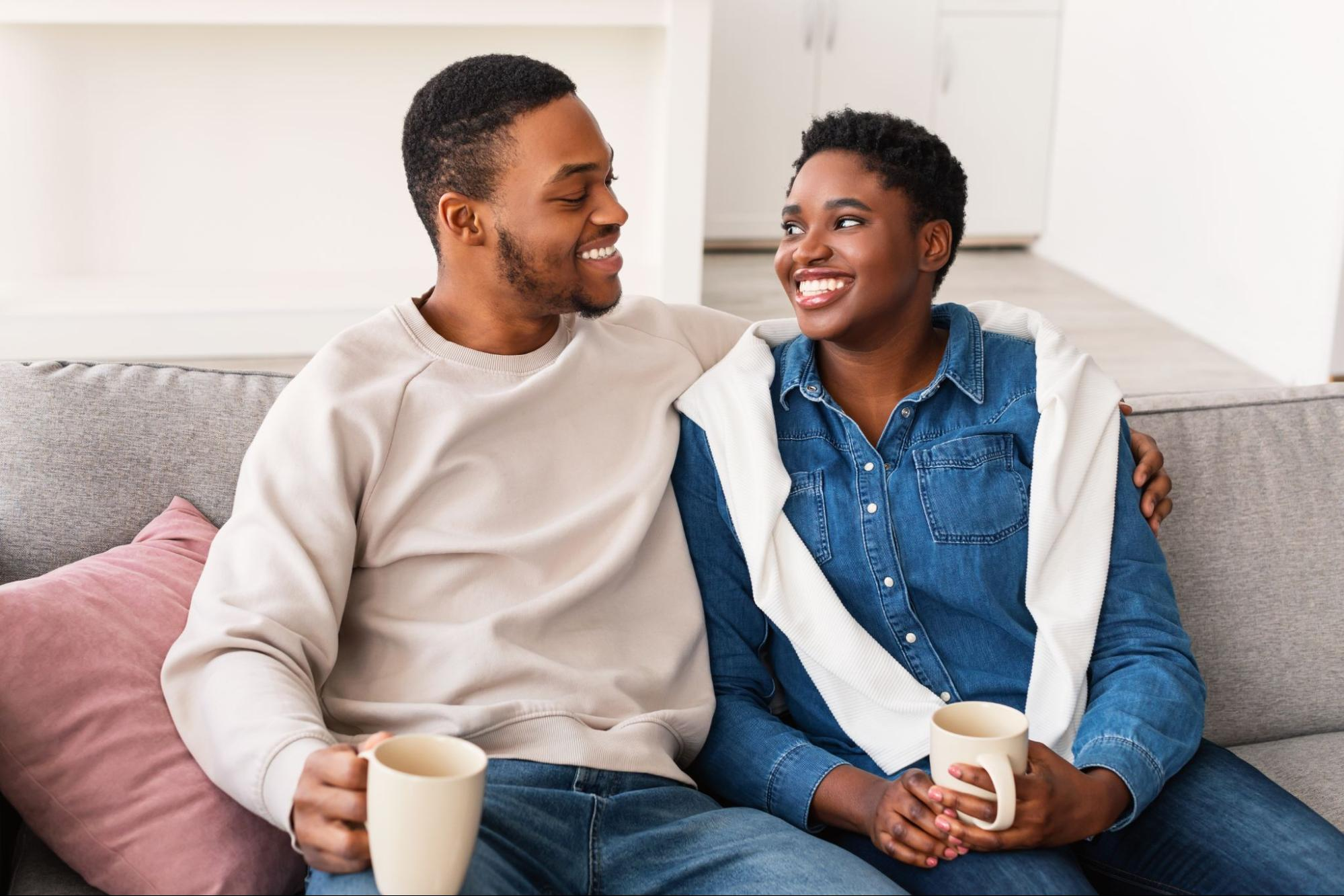 A smiling couple sits on their couch and drinks coffee