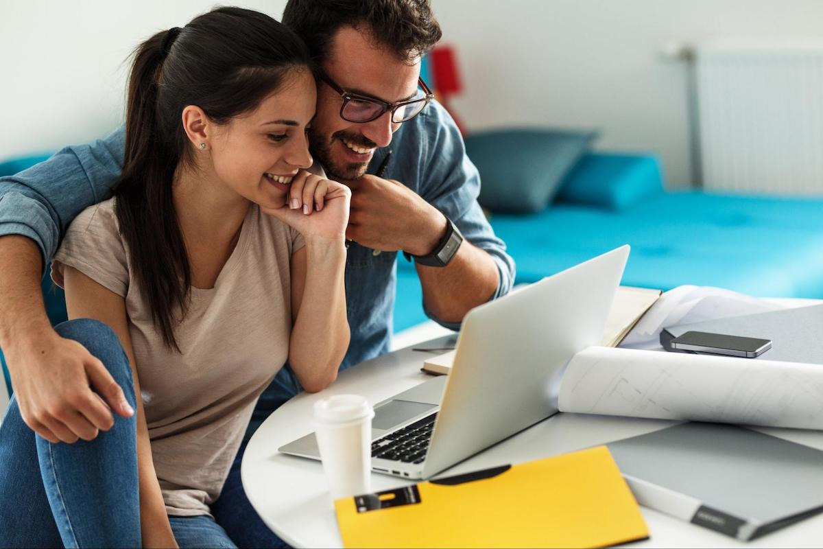A smiling couple looks at their variable expenses on a laptop