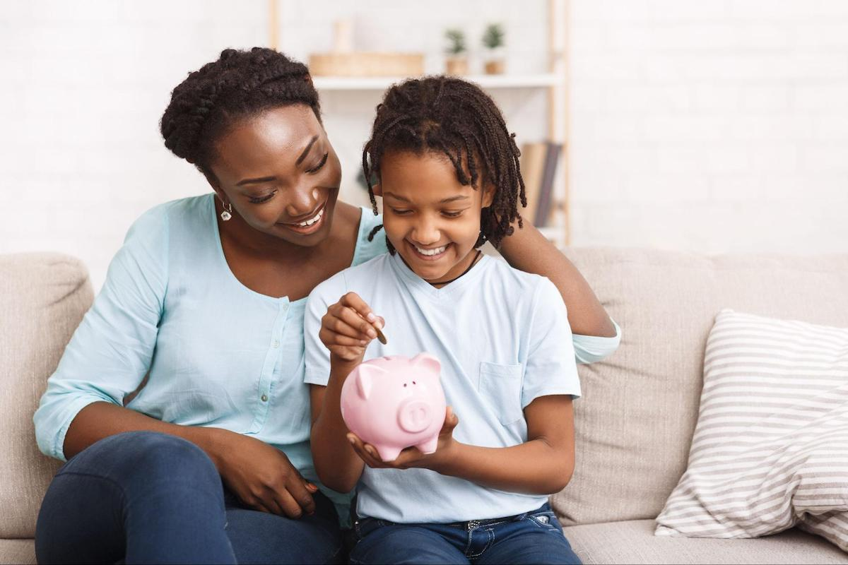 A mother and daughter put a coin in a piggy bank