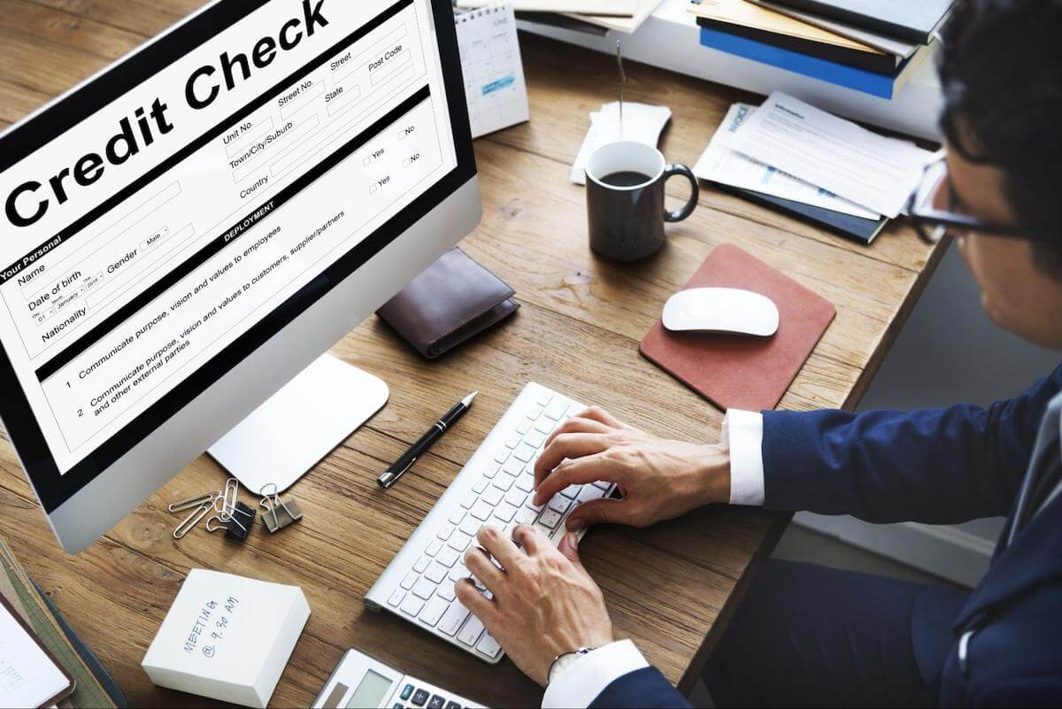 A man performs a credit check on a computer