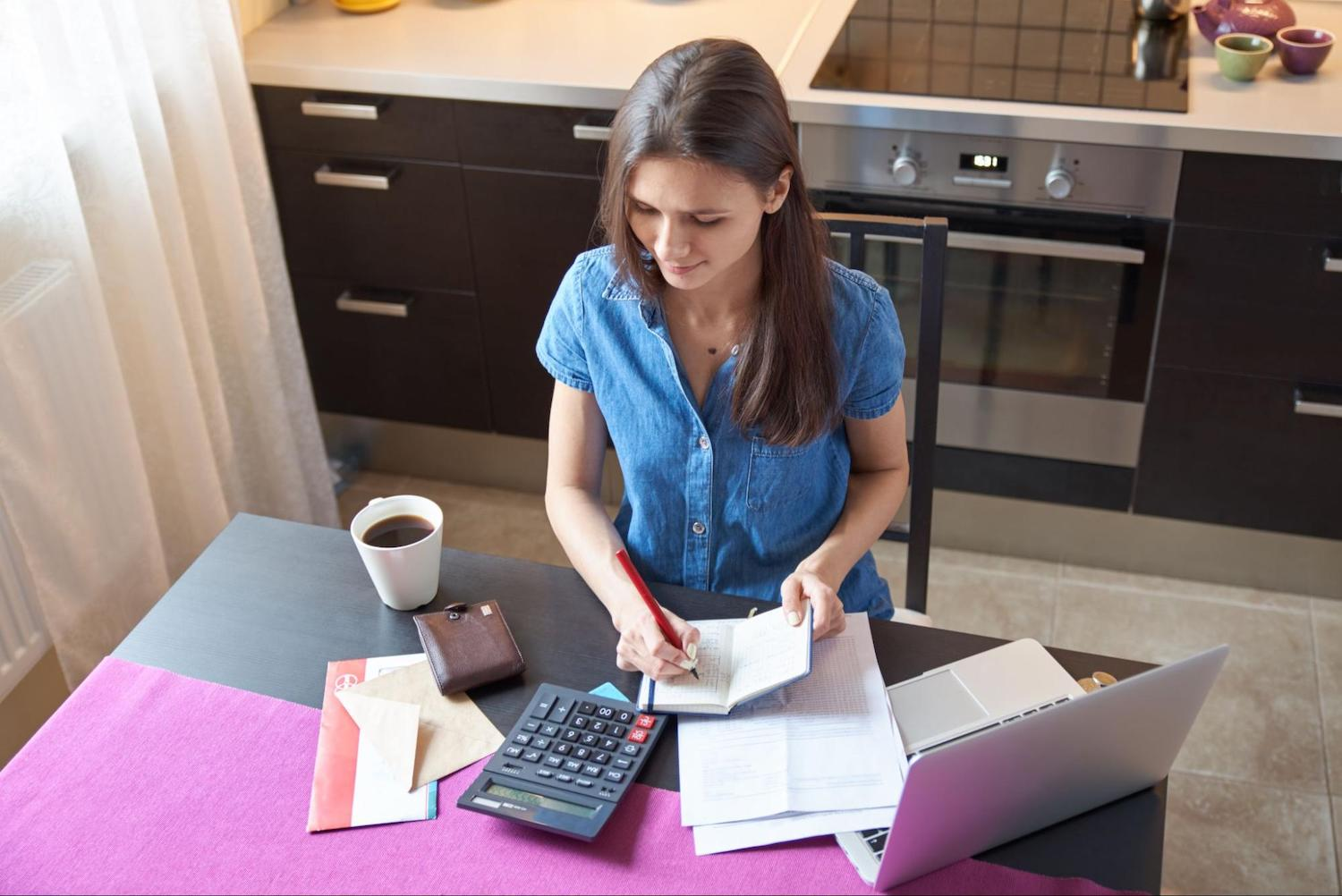 A woman uses a calculator to plan her budget