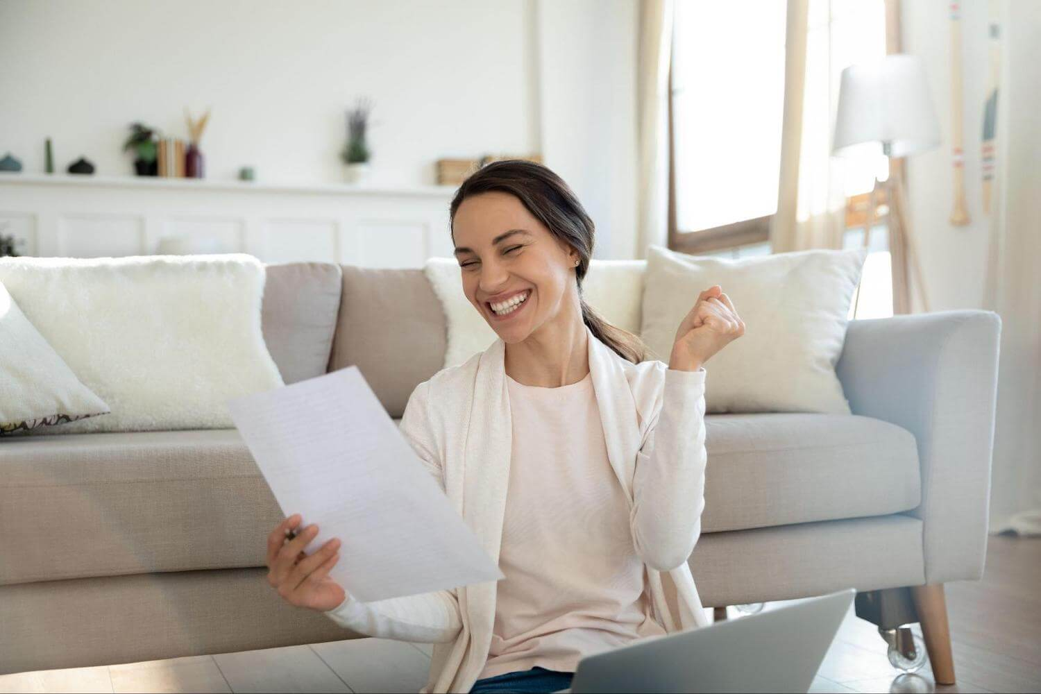 A woman celebrates while looking at a piece of paper