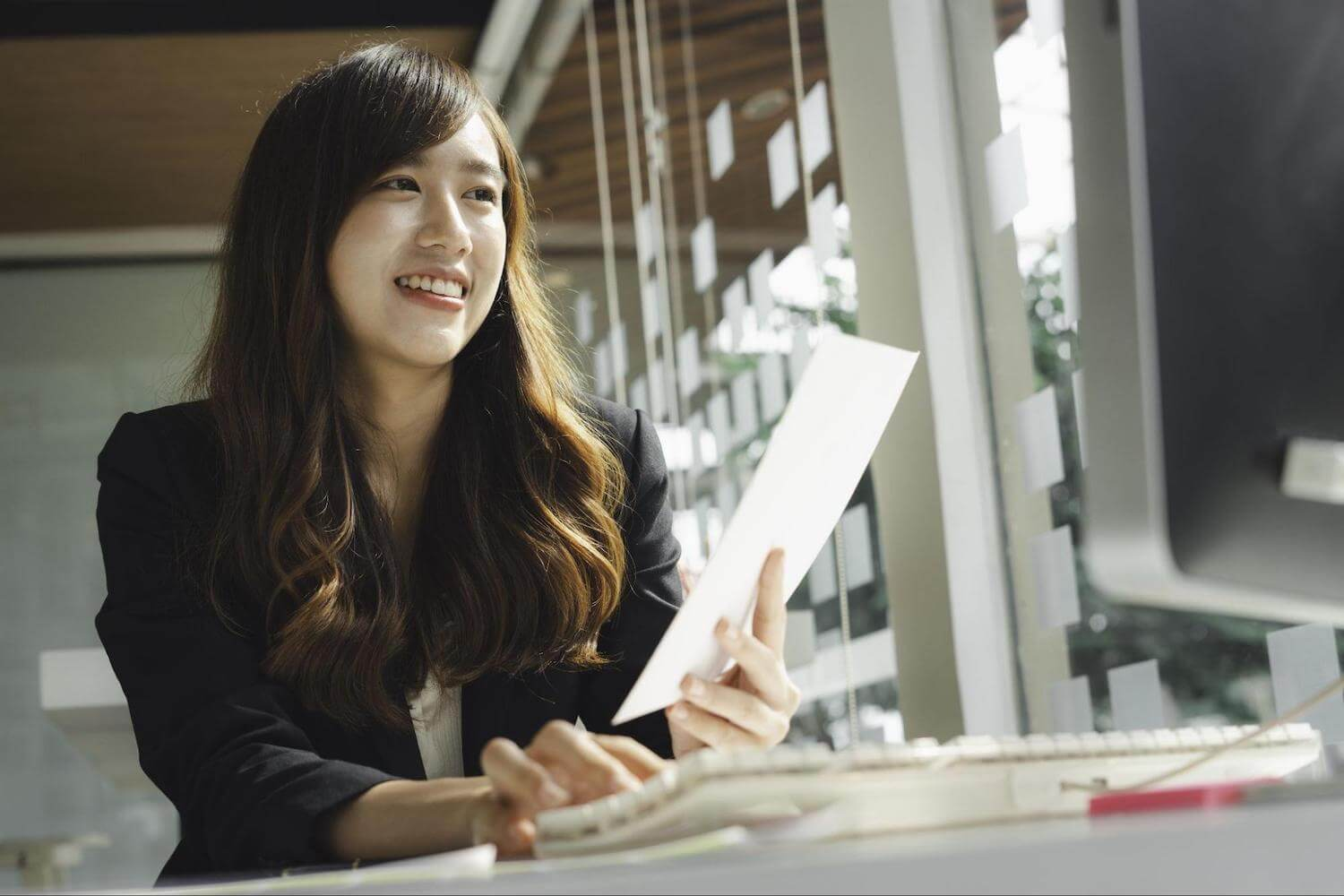 Do student loans affect credit score: A smiling woman holds a piece of paper while using a computer