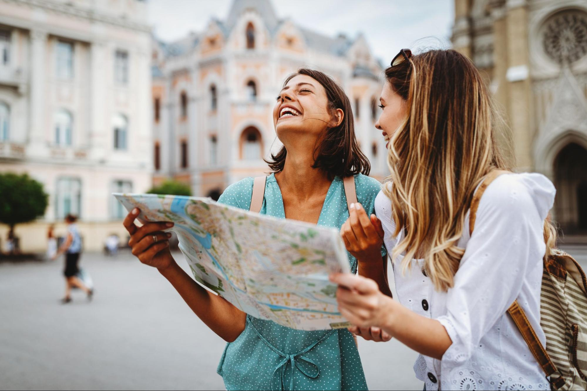 How to travel on a budget: Two women use a map while sightseeing