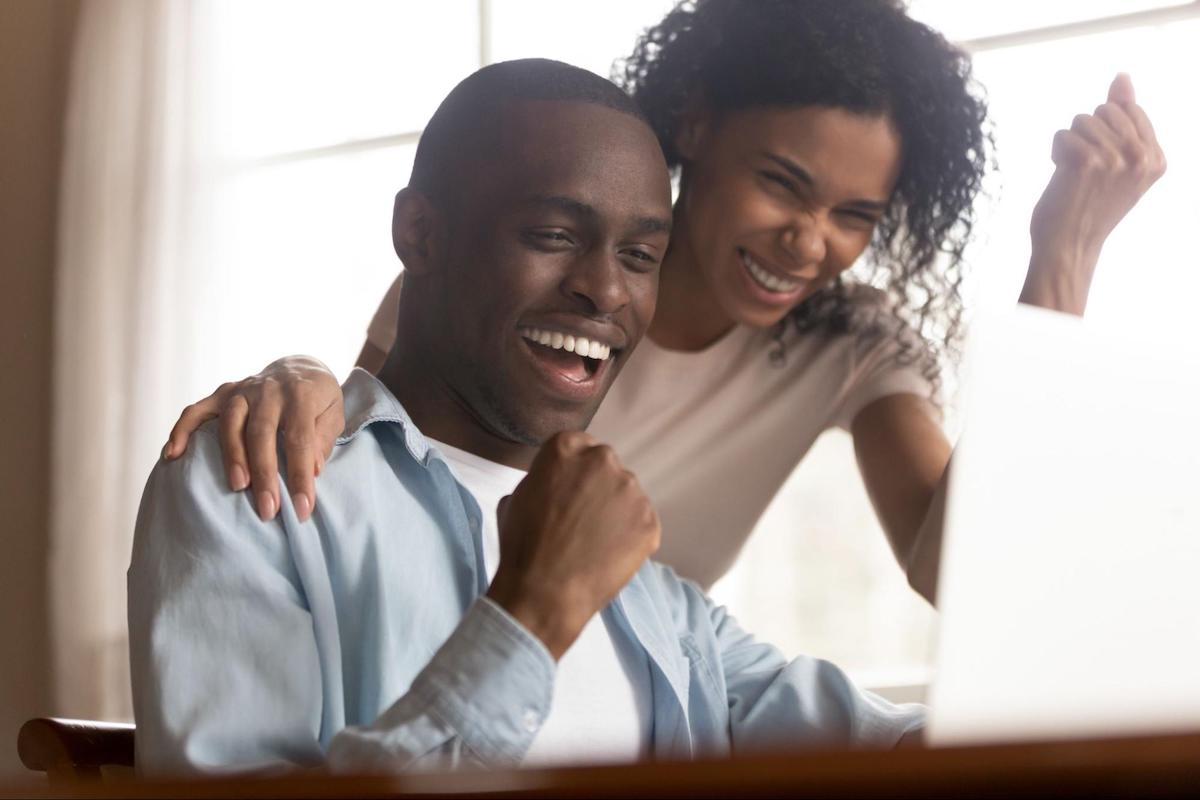 A celebrating couple looks at a laptop screen