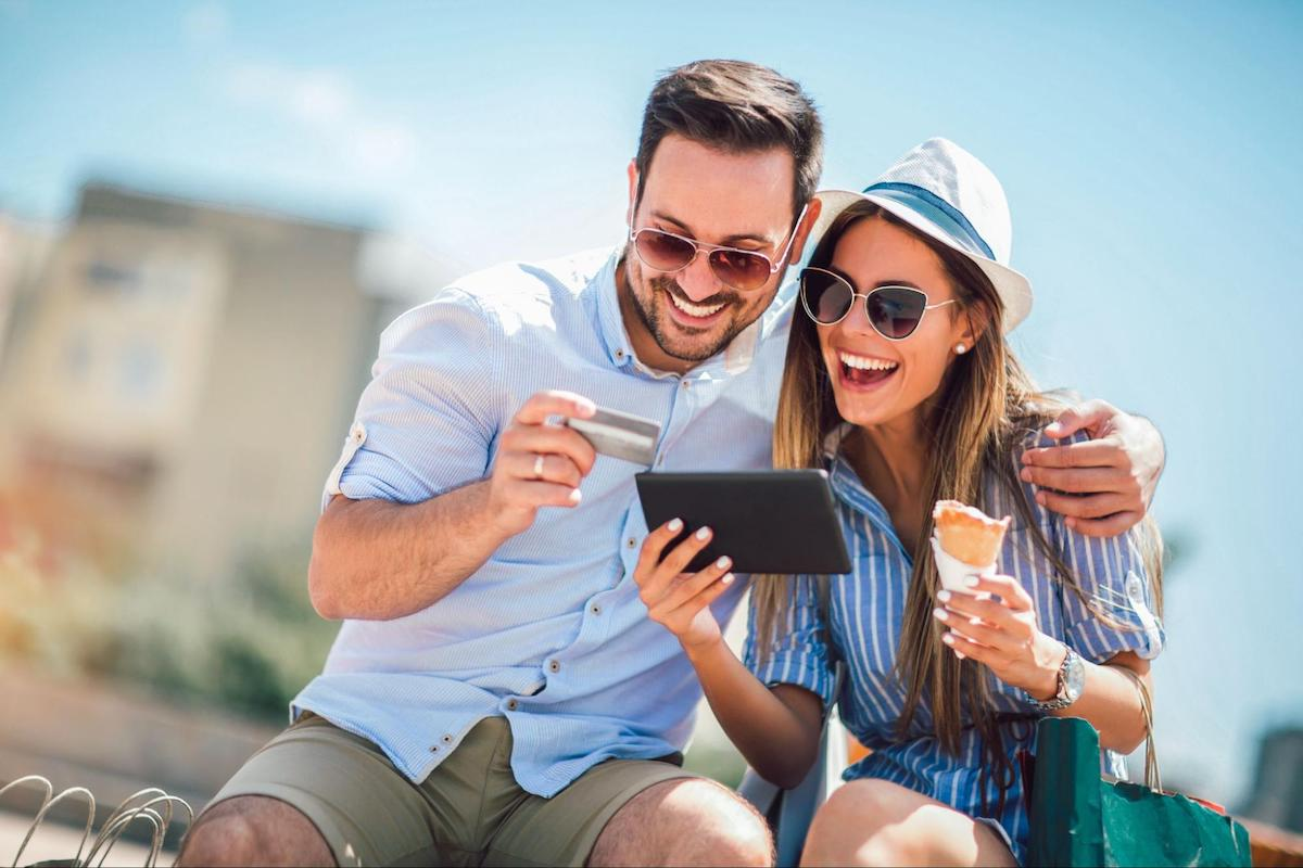 A happy couple uses a credit card on a tablet