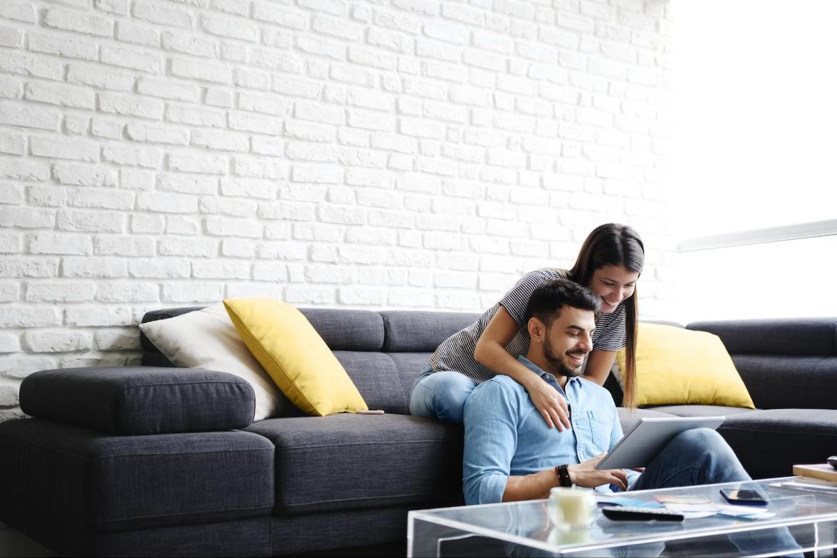 A happy couple uses a tablet together in their home