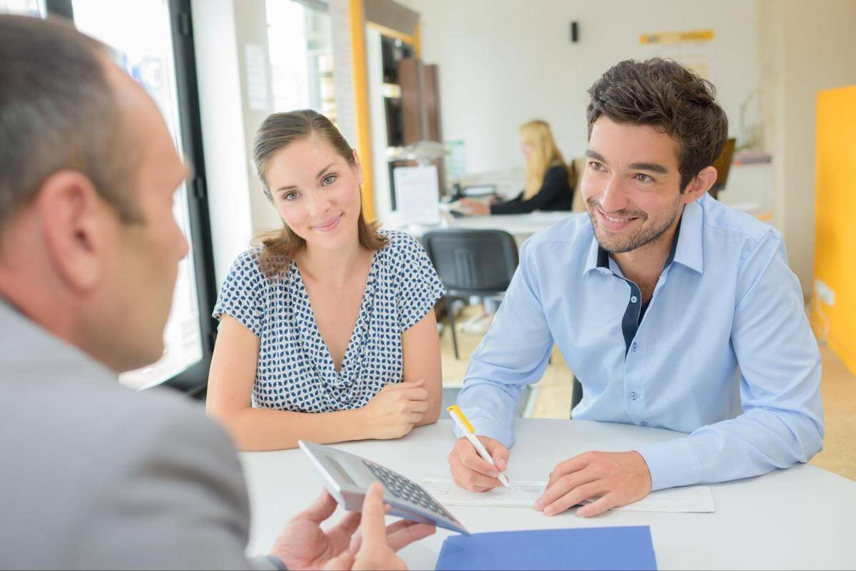 Debt consolidation loan interest rates: A couple writes a check while meeting with a lender