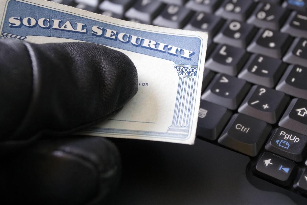 How to report identity theft: A gloved hand of a hacker holds a Social Security card