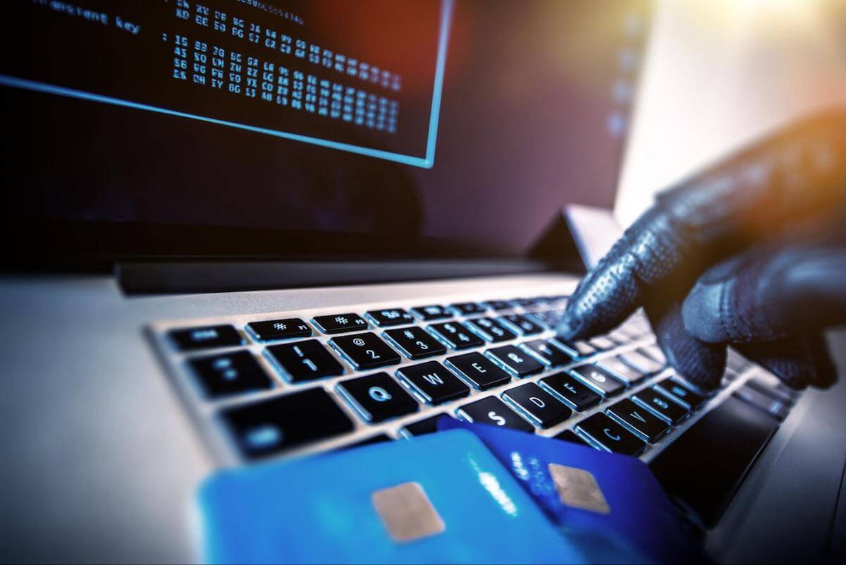 Identity theft protection: The gloved hand of a hacker type on a laptop