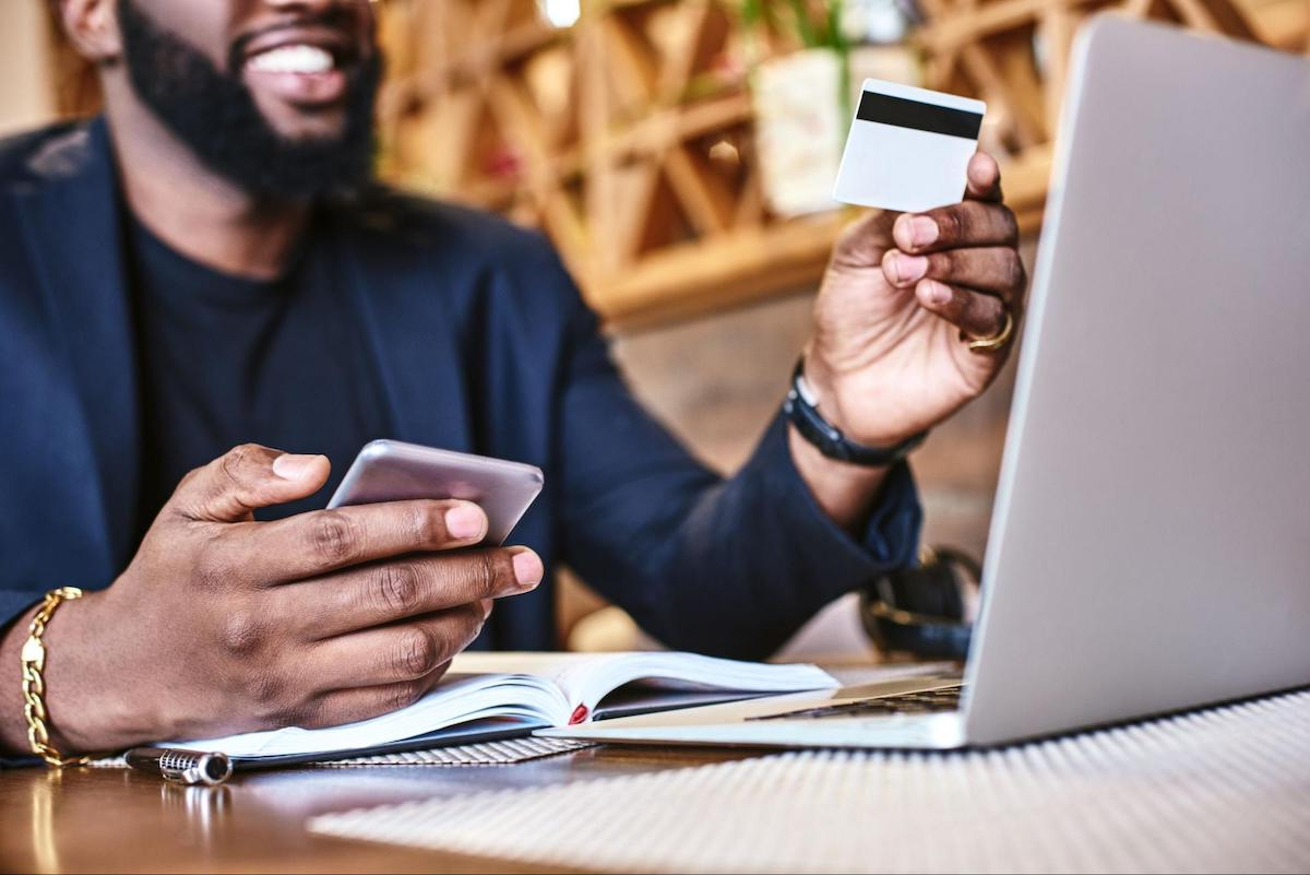 How long does a balance transfer take: Smiling man looks at his credit card while holding his cellphone