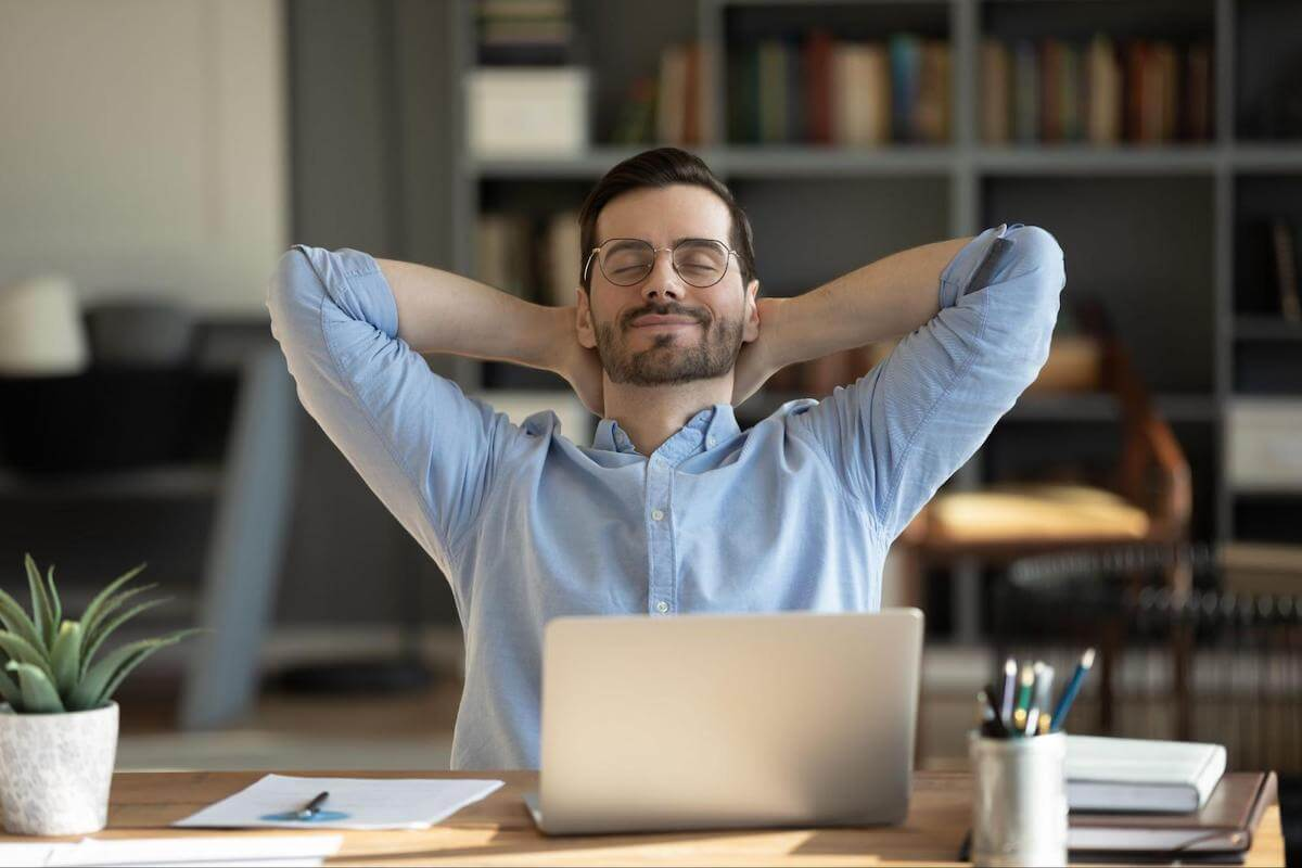 A man relaxes at his desk with his arms behind his head