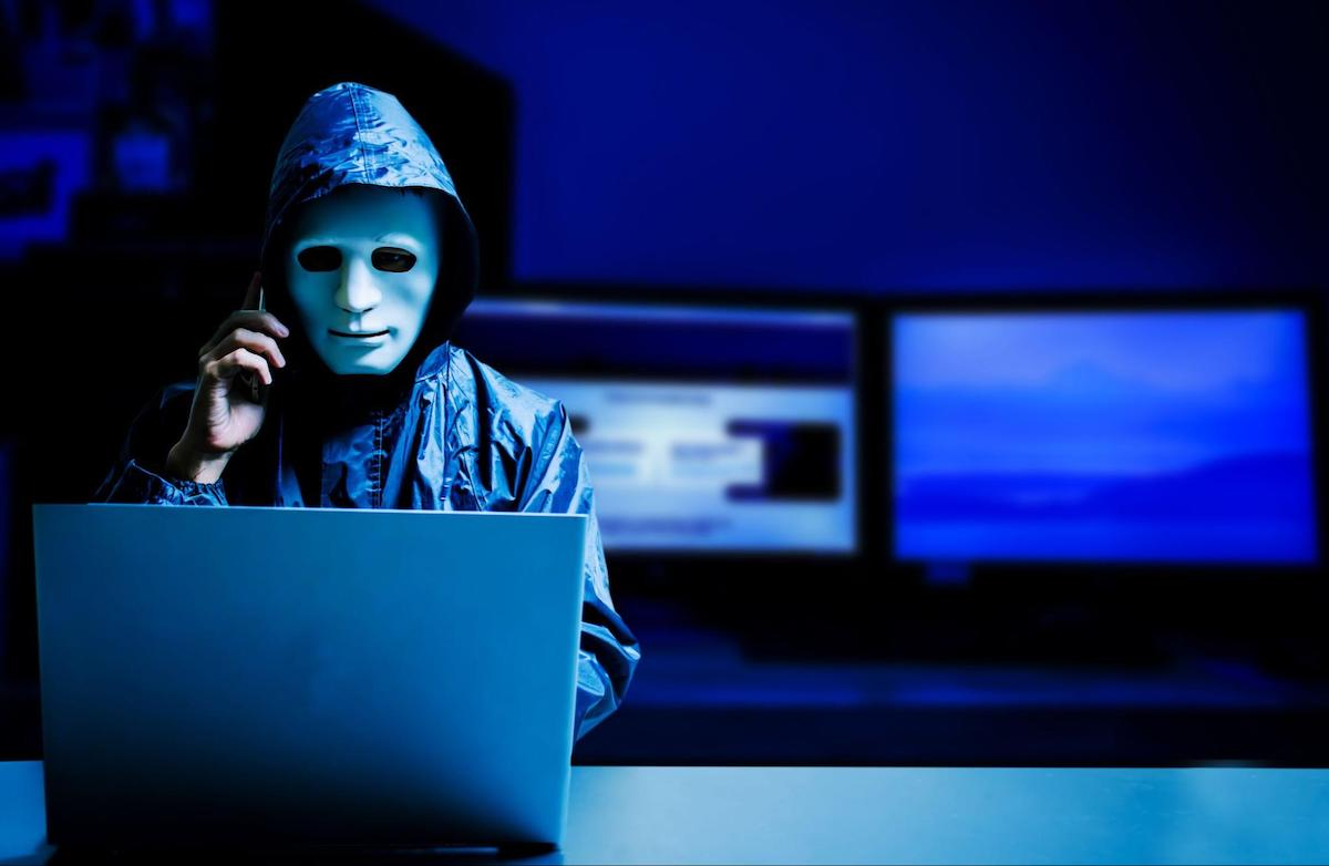 SIM swap: A masked hacker sits behind a laptop and talks on a cellphone