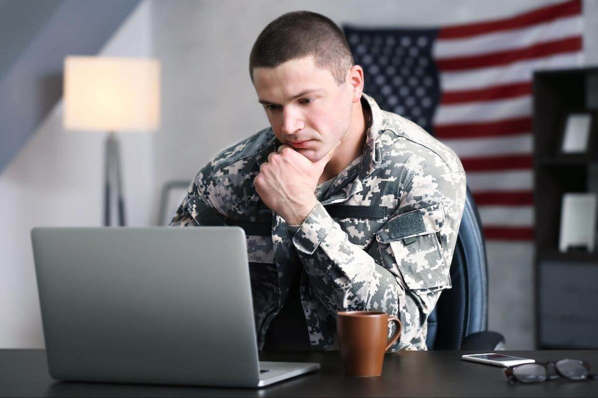 A soldier in camouflage looks at a laptop screen