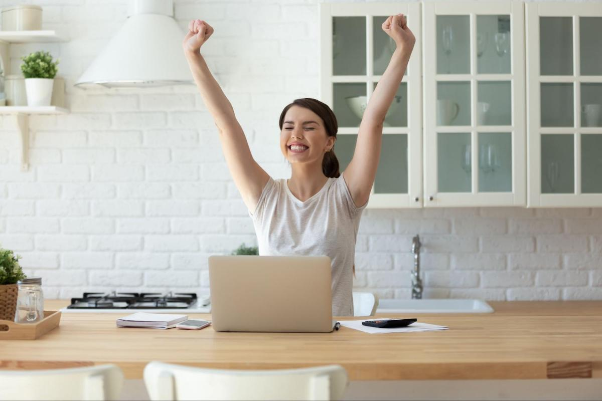 A woman uses her laptop in her kitchen and celebrates with her arms in the air