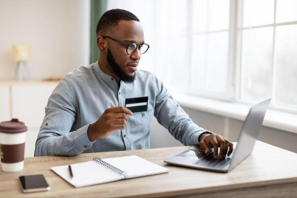 Man holds credit card and types on computer
