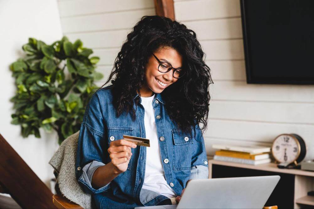 Smiling woman holds credit card while typing on laptop