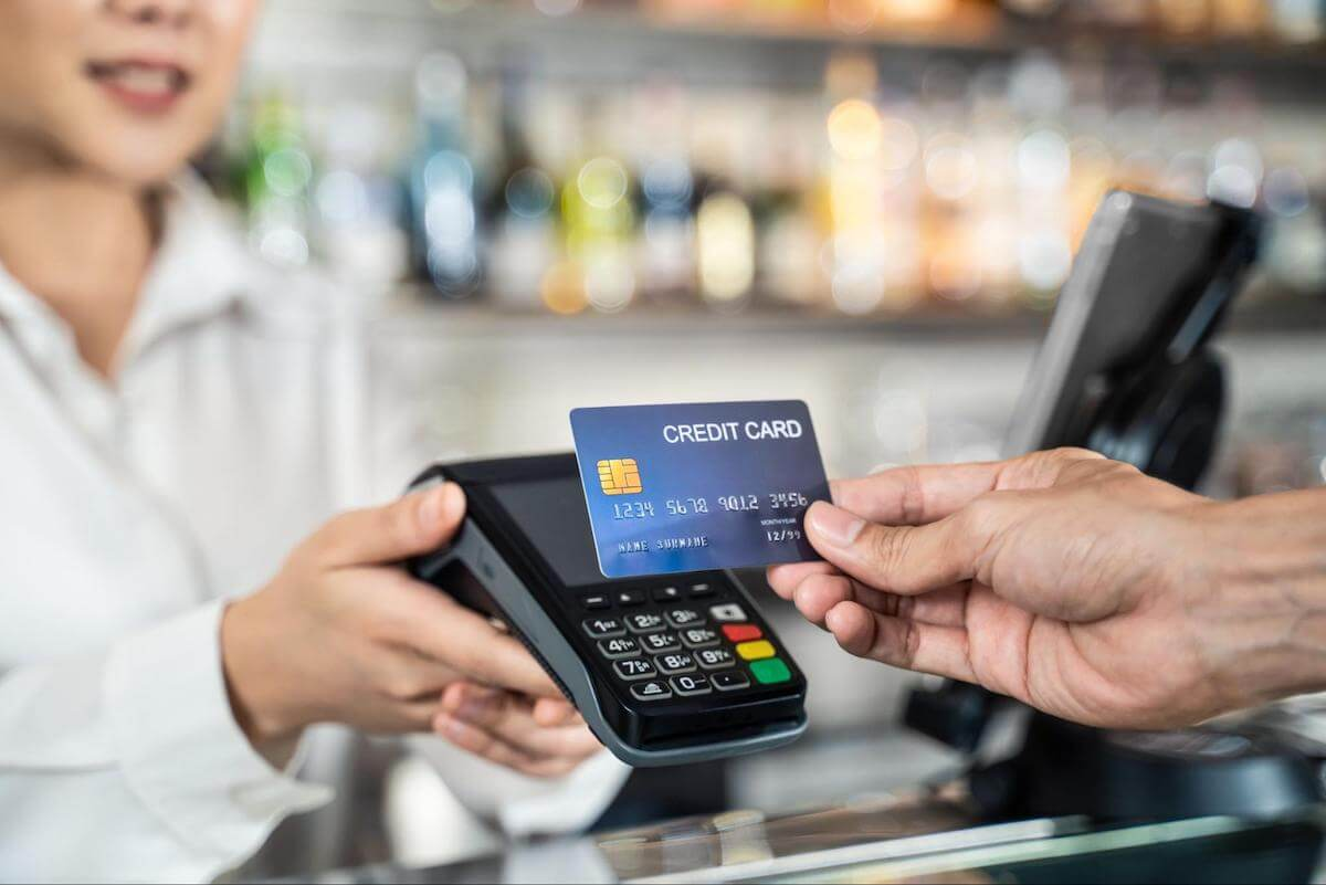 How do credit card companies make money: A closeup of a person making a contactless payment with a credit card