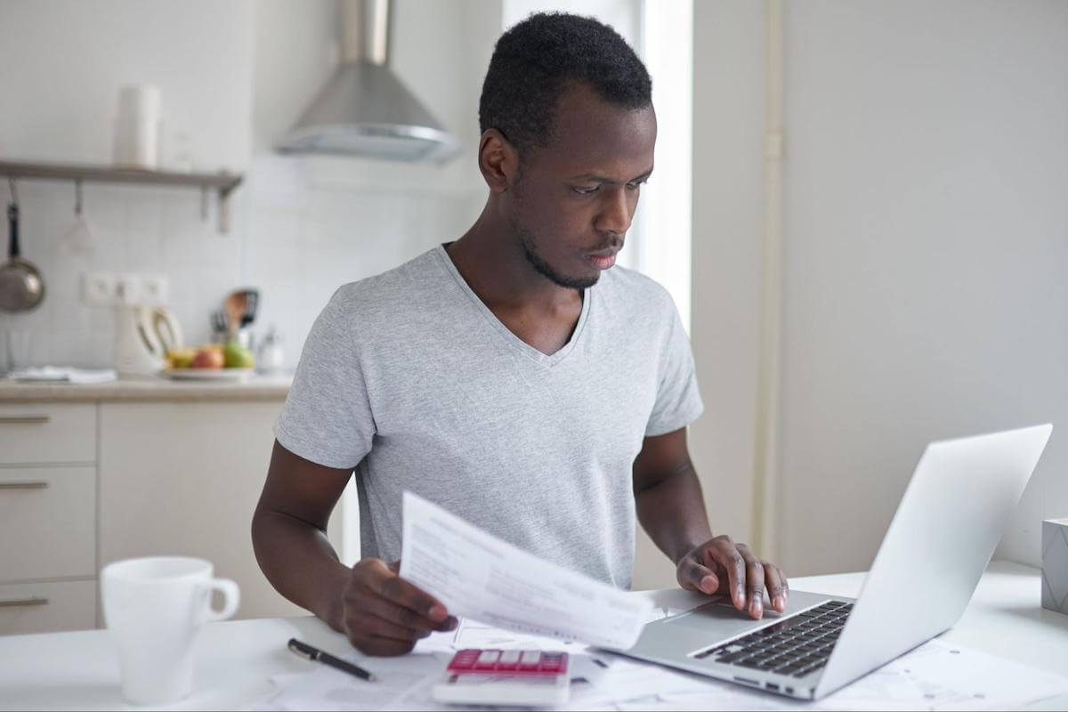 A college student applies for a loan on his laptop