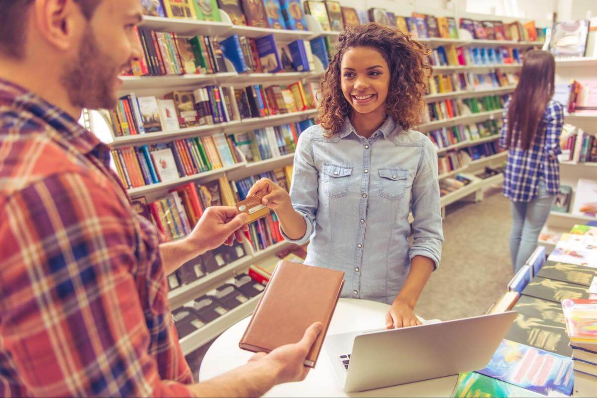 Average credit card debt for college students: A student uses a credit card to make a purchase in the bookstore
